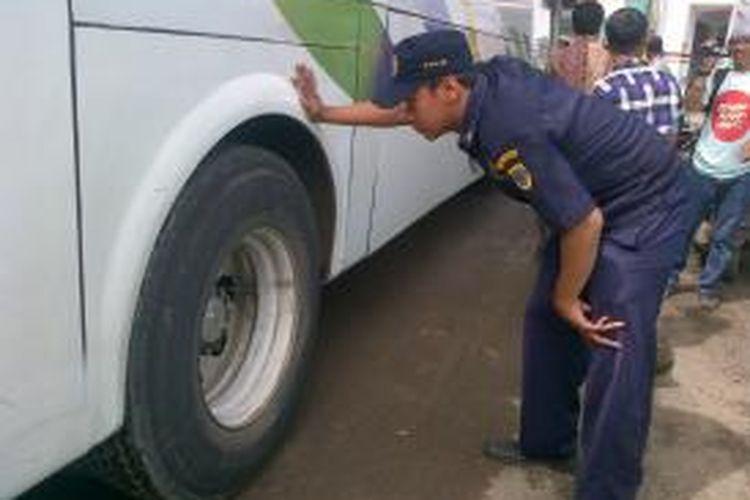 Petugas dari Dinas Perhubungan Brebes, Jawa Tengah, melakukan cek ban bus dalam rangka sidak kelaikan jalan di Terminal Tanjung, Selasa (24/12/2013).
