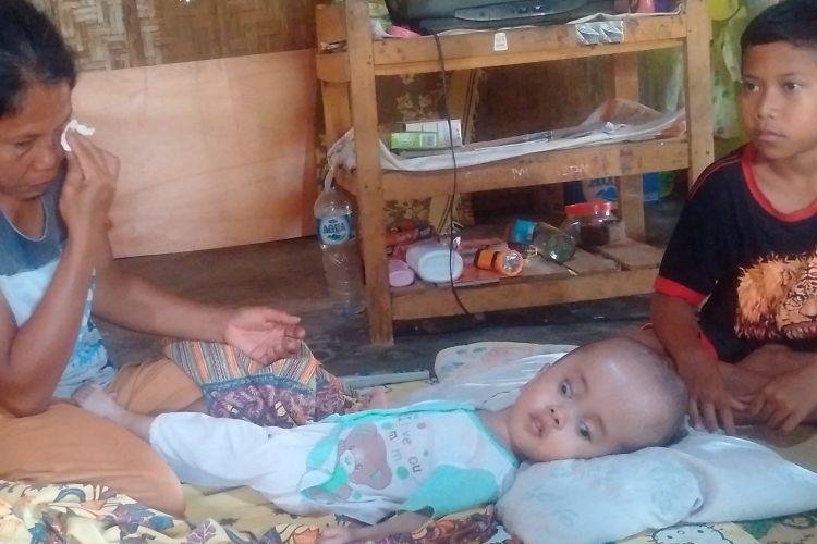 SEKA AIR MATA--Kasmiati, seorang buruh tani asal Ponorogo menyeka air matanya saat menceritakan derita anaknya yang terserang hydrocephalus dan suaminya yang terserang kanker kulit stadium empat di rumahnya, Dusun Sekuwung, Desa Kedung Banteng, Kecamatan Sukorejo, Kabupaten Ponorogo, Jawa Timur, Jumat ( 31 / 3 / 2017) siang.