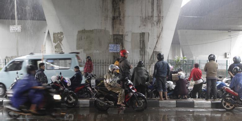 Pengendara motor berteduh di bawah jembatan di kawasan Slipi, Jakarta, Jumat (14/11/2014). Badan Meteorologi, Klimatologi, dan Geofisika (BMKG) memperkirakan wilayah DKI Jakarta diguyur hujan dengan intensitas ringan hingga sedang pada siang hingga malam hari. KOMPAS IMAGES/RODERICK ADRIAN MOZES