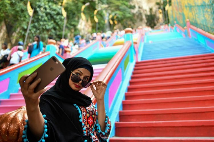 A woman takes selfies in front of the newly-painted 272-steps staircase leading to Malaysias Batu Caves Hindu temple in Kuala Lumpur on August 30, 2018. (Photo by Manan VATSYAYANA / AFP)        (Photo credit should read MANAN VATSYAYANA/AFP/Getty Images)