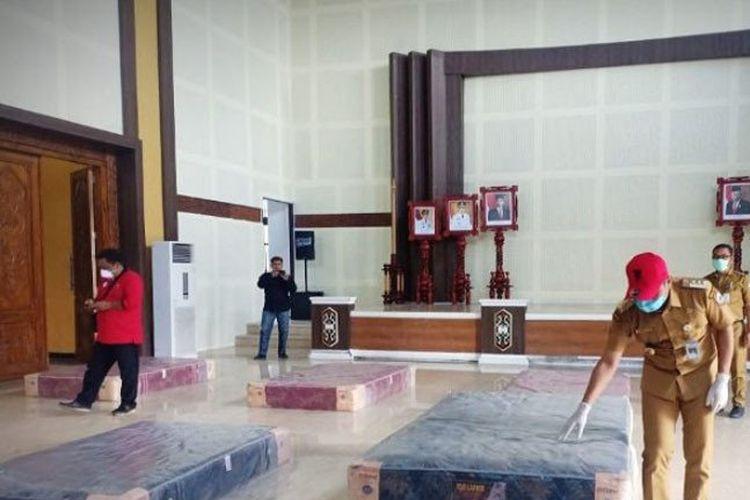 Bupati Kotawaringin Timur Supian Hadi (topi merah) memantau pekerja menata tempat tidur di rumah jabatan bupati yang akan dimanfaatkan menjadi tempat beristirahat tim medis penanganan COVID-19 di Sampit, Senin (6/4/2020).