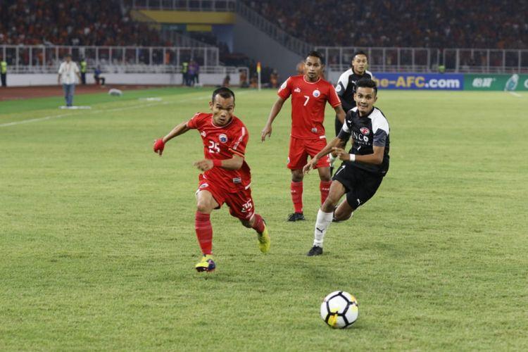 Pemain Persija, Riko Simanjuntak (kiri) dibayangi pemain Home United pada laga leg kedua semifinal Piala AFC 2018 di SUGBK, Selasa (15/5/2018).