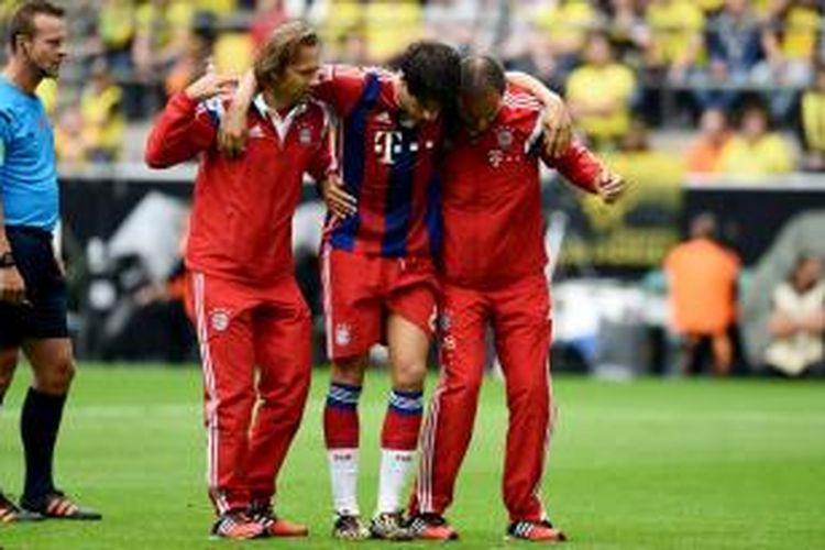Gelandang Bayern Muenchen, Javi Martinez (tengah) saat dipapah ke luar lapangan karena mengalami cedera ketika menghadapi Borussia Dortmund, Rabu (13/8/2014).