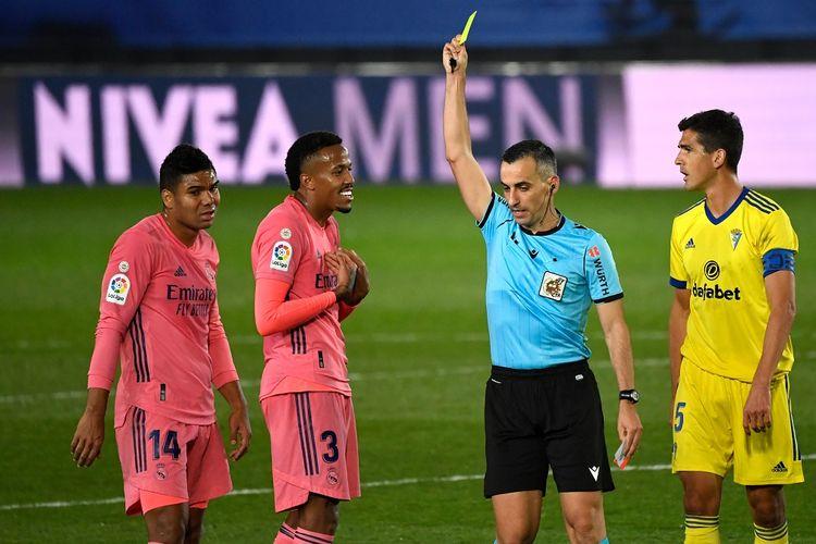 Pemain Real Madrid, Eder Militao (3), saat diganjar kartu kuning oleh wasit Santiago Jaime Latre dalam laga kontra Cadiz CF, 17 Oktober 2020.
