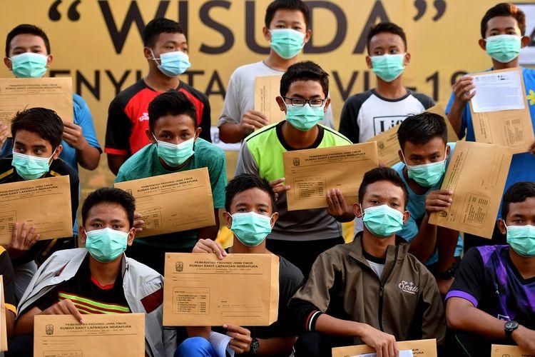 Sejumlah santri asal Ponpes Gontor berpose ketika mengikuti wisuda penyintas  COVID-19 di halaman Rumah Sakit Lapangan Surabaya, Jawa Timur, Selasa (28/7/2020). Berdasarkan data Satgas penanganan COVID-19 menyatakan jumlah pasien sembuh di Jawa Timur pada (28/7) sebanyak 401 pasien sehingga total pasien yang dinyatakan sembuh tercatat 13.081 orang. ANTARA FOTO/Zabur Karuru/hp.