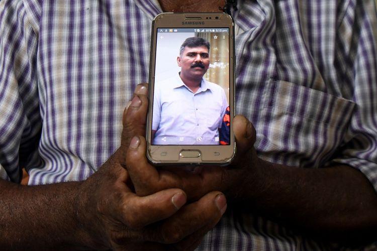 Foto yang diambil pada 26 April 2019 memperlihatkan Velusami Raju ketika memegang foto sang anak, Ramesh Raju, yang menjadi pahlawan karena tewas ketika menghentikan pelaku bom bunuh diri di Gereja Zion, Batticaloa, Sri Lanka, pada Minggu pekan lalu (21/4/2019).