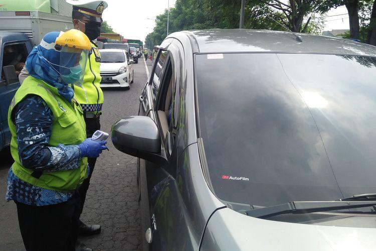 Anggota kepolisian dan petugas kesehatan, saat memeriksa salah satu kendaraan di pos cek poin yang berada di exit tol Kebomas.
