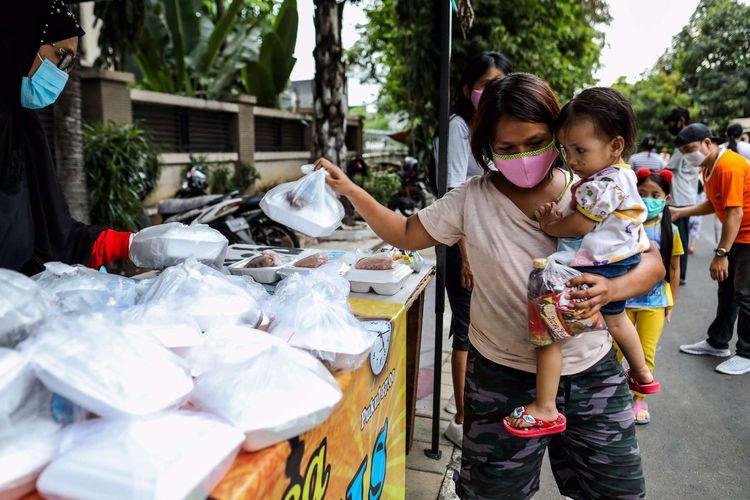 Warga mengambil takjil yang disediakan di Jl. Cempaka Warna RT 05 RW 06, Cempaka Putih Timur, Jakarta Timur, Kamis (21/5/2020). Setiap hari selama Ramadan, relawan dan donatur membagikan 400 hingga 600 takjil kepada warga kurang mampu dan terdampak virus corona COVID-19.