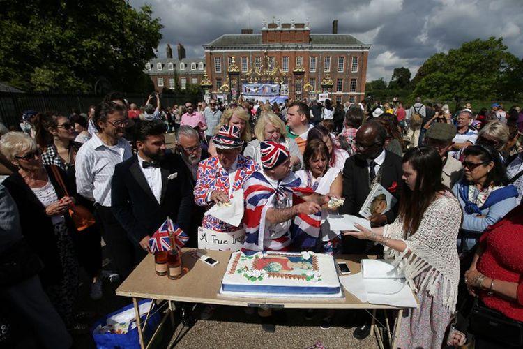 John Loughrey (tengah) membagikan irisan kue yang dihias dengan gambar Putri Diana, kepada anggota warga London yang berkumpul di luar gerbang Istana Kensington, Kamis (31/8/2017).