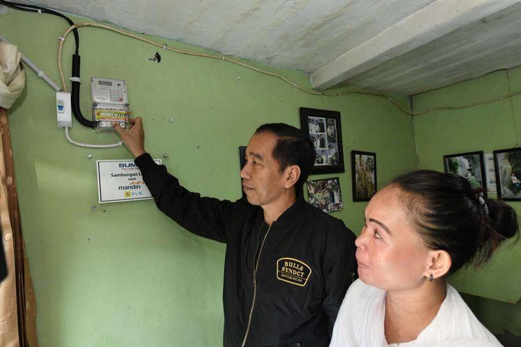 Presiden RI Joko Widodo mengisikan token dan menyalakan listrik di salah satu rumah warga di Bantarjati, Bogor, Jawa Barat, Minggu (2/1/2018). Penyerahan ini merupakan bagian dari pemberian 60.000 sertifikat listrik gratis bagi warga di Jawa Barat.