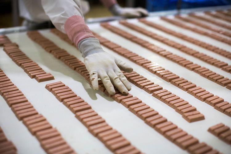 Dalam gambar yang diambil pada tanggal 24 Agustus 2017, seorang pekerja Jepang memeriksa batang KitKat rasa stroberi di jalur produksi di pabrik KitKat di Inashiki, prefektur Ibaraki, timur laut Tokyo.