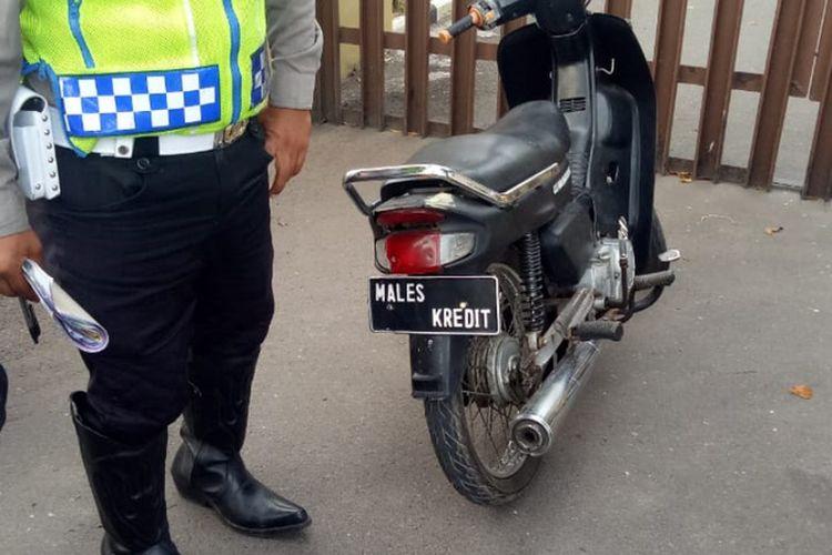 Seorang anggota Satlantas Polres Garur memunjukan sepeda motor berplat nomor tidak lazim karena hanya bertuliskan Malas Kredit (Foto Dok Satlantas Polres Garut)