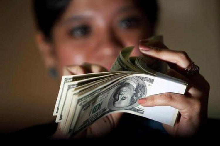 Petugas kasir menghitung uang dollar As di Kantor BNI Pusat.