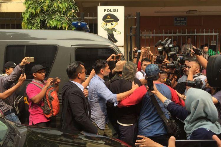 Jeremy Thomas (45) menemani anaknya yang menjadi tersangka kasus pembelian narkoba, Axel Matthew Thomas (19), menuju ruang tahanan Mapolda Metro Jaya, Rabu (19/7/2017).
