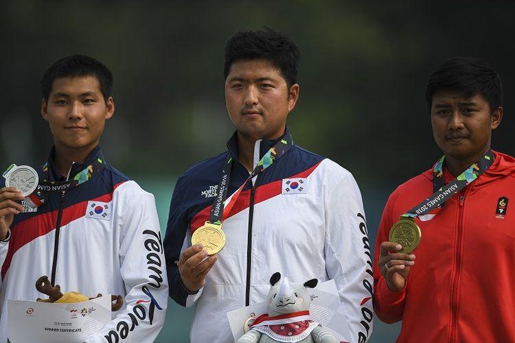 Dalam foto ini terlihat atlet panahan Korea Selatan Lee Woo-seok yang merah medali perak dan atlet Indonesia Ega Agata Salsabilla mengapit sang juara Kim Woo-jin dalam penyerahan medali nomor recurve individual putra di Asian Games Jakarta 2018.