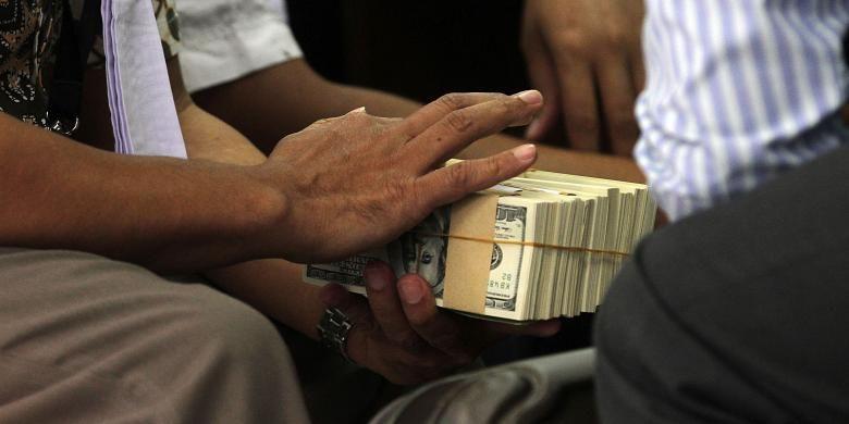 ILUSTRASI SUAP: Jaksa Penuntut Umum menyiapkan barang bukti berupa uang pecahan dolar Amerika Serikat dalam sidang mantan Kepala Satuan Kerja Sementara Pelaksana Kegiatan Hulu Minyak dan Gas Bumi (SKK Migas) Rudi Rubiandini di Pengadilan Tindak Pidana Korupsi di Jakarta, Selasa (25/2/2014). Dalam sidang tersebut diperiksa sebagai saksi Ketua Komisi VII DPR RI Sutan Bhatoeghana dan mantan Sekjen Kementerian ESDM Waryono Karno terkait pengurusan tender proyek di SKK Migas. TRIBUNNEWS/DANY PERMANA