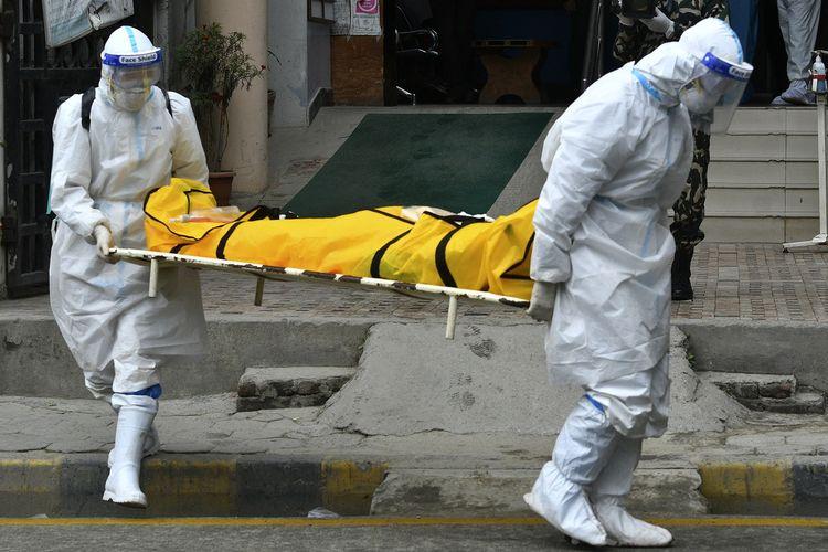 Personel pasukan Nepal yang menggunakan APD membawa mayat yang meninggal karena Covid-19 pada Rabu (5/5/2021). [PRAKASH MATHEMA/AFP]