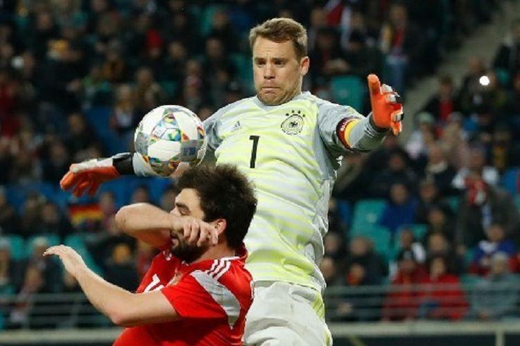 Manuel Neuer melompat lebih tinggi daripada Georgiv Dzhikiya pada laga persahabatan Jerman vs Rusia di Leipzig, 15 November 2018.