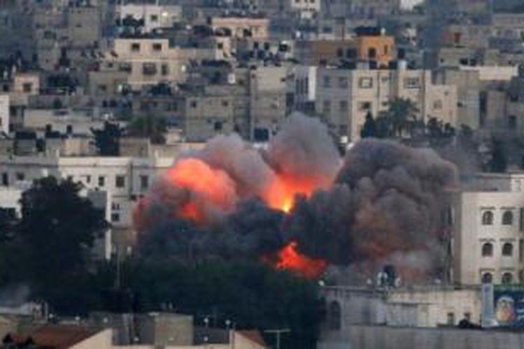 Sebuah bola api terlihat saat roket Israel menghantam sebuah bangunan di Jalur Gaza, Rabu (9/7/2014). Setelah tiga hari operasi Protective Edge digelar militer Israel, 73 warga Palestina tewas dan ratusan lainnya terluka.