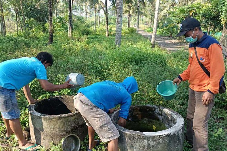 Warga kerja bakti di Pedukuhan Kriyan, Kalurahan Karangwuni, Kapanewon Temon, Kabupaten Kulon Progo, Daerah Istimewa Yogyakarta. Mereka membersihkan buis beton berisi air di sekeliling kampung pasca puluhan warga di dua RT diduga terjangkit DBD.