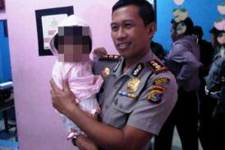 Balita 17 bulan yang diduga sebagai korban penculikan saat digendong Kapolres Lombok Barat AKBP Yulianus Yulianto.