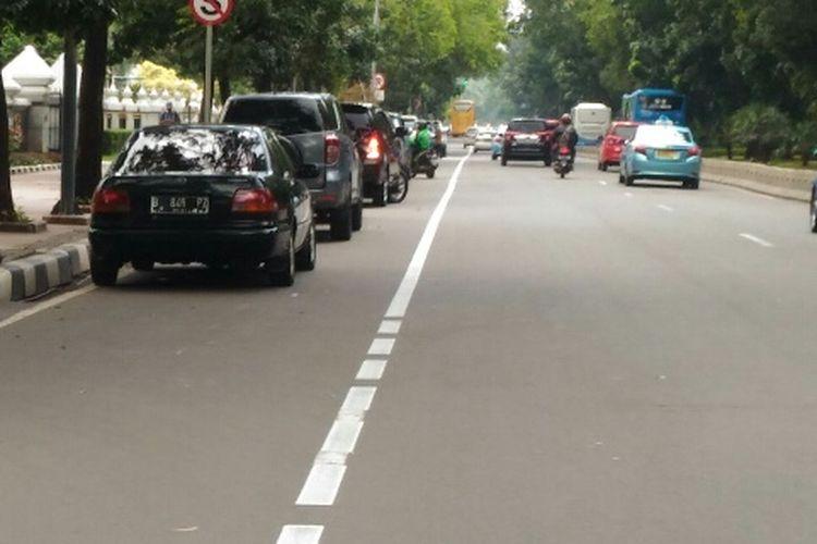 Lajur paling kiri yang diperuntukkan bagi pengendara motor dijadikan tempat parkir mobil di Jalan Medan Merdeka Barat, Rabu (24/1/2018).