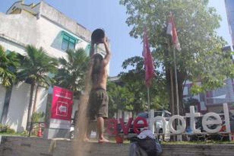 Dodok Putra Bangsa (37), warga Kampung Miliran, Kota Yogyakarta, melakukan aksi teatrikal di depan Fave Hotel, Yogyakarta, Rabu (6/8). Aksi itu untuk menyuarakan keringnya sumur warga Miliran yang diduga terkait dengan keberadaan Fave Hotel di wilayah itu.