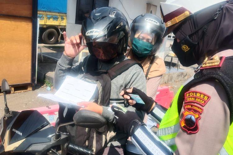 Polisi mengecek kelengkapan dokumen pengendara luar kota yang melintasi posko cheint point PPKM Darurat di depan Terminal Bus Kota Tegal, Jumat (16/7/2021). (Dok. Polres Tegal Kota).
