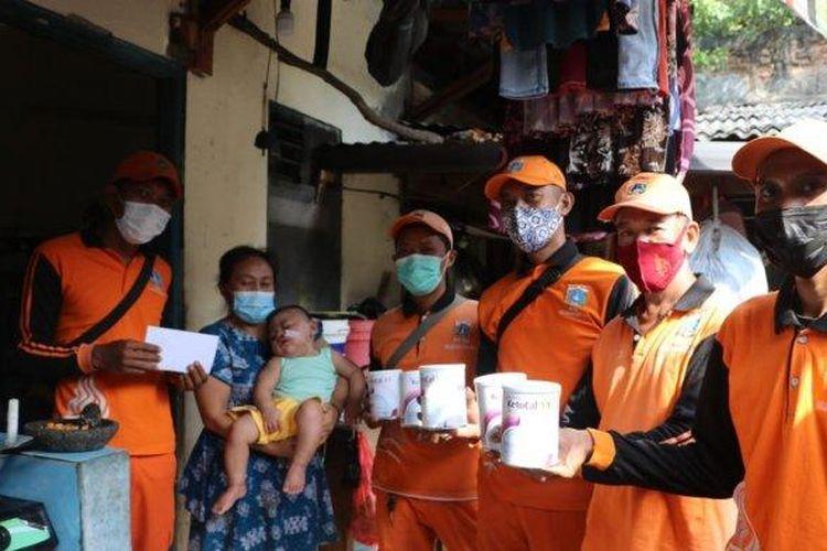Sejumlah petugas PPSU menyambangi kediaman Kenzi dan memberikan bantuan enam kaleng susu khusus dan donasi kepada Kenzi sebelum lebaran.