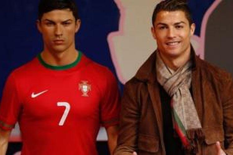 Bintang Real Madrid Cristiano Ronaldo (kanan) berfoto di samping patung lilin dirinya.