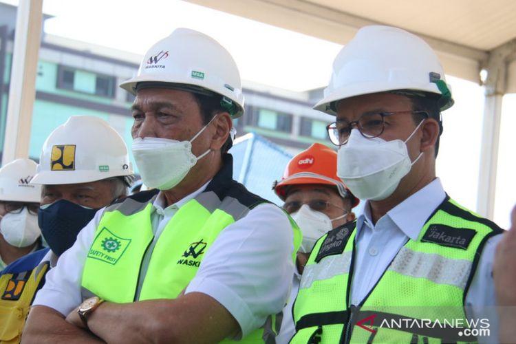 Gubernur DKI Jakarta Anies Baswedan (kanan) berdiri di sebelah Menteri Kordinator Bidang Kemaritiman dan Investasi Luhut Binsar Panjaitan (kiri) saat meninjau kondisi terakhir pembangunan tanggul laut di Muara Baru, Penjaringan, Jakarta Utara, Kamis (16/9/2021).