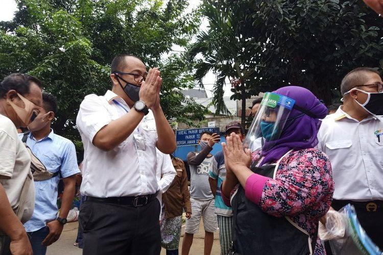 Direktur Utama Perumda Pasar Jaya Arief Nasrudin (kiri) berdialog dengan pedagang sayur di Pasar Perumnas Klender, Jakarta Timur, terkait sosialisasi perdana ganjil genap operasional kios, Senin (15/6/2020).