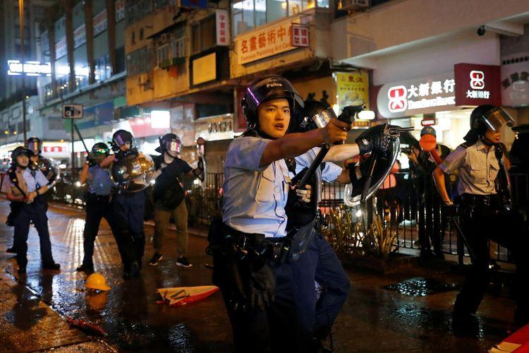 Anggota polisi menodongkan pistol ke arah peserta demo Hong Kong di Tsuen Wan, pada 25 Agustus 2019.
