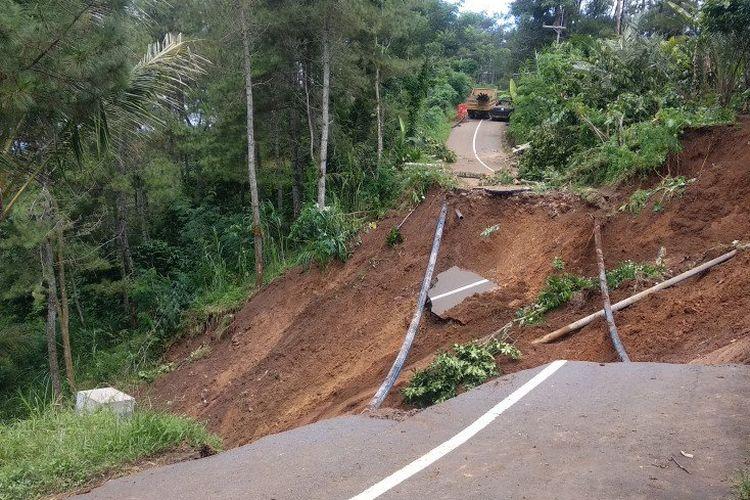 Pekerja beraktivitas di sekitar lokasi jalan antarkecamatan Trenggalek-Bendungan yang amblas terseret longsor di Desa Suren Lor, Trenggalek, Senin (6/4/2020).