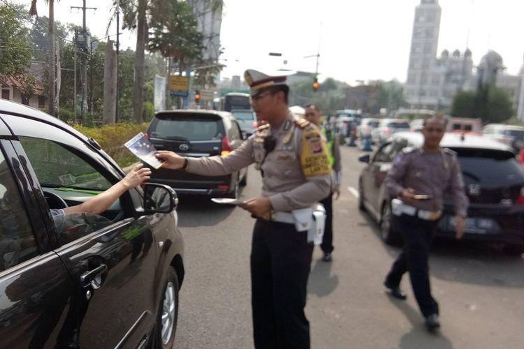 Seorang petugas kepolisian sedang membagikan flyer di Simpang Gadog, Ciawi, Sabtu (12/10/2019). Hal tersebut dilakukan sebagai bentuk sosialisasi pelaksanaan sistem 2-1 yang akan diuji coba pada tanggal 27 Oktober 2019 mendatang.