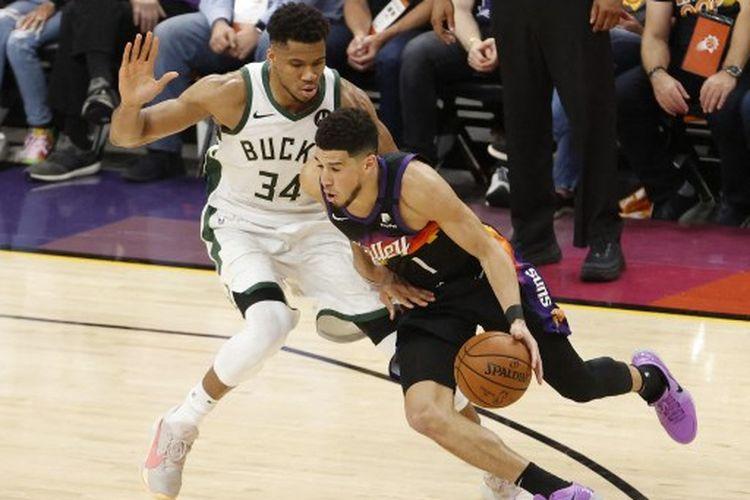Devin Booker (kanan) berduel dengan Giannis Antetokounmpo (kiri) pada gim kedua final NBA 2020-2021 yang mempertemukan Pheonix Suns vs Milwaukee Bucks di Phoenix Suns Arena, Jumat (9/7/2021) pagi WIB.