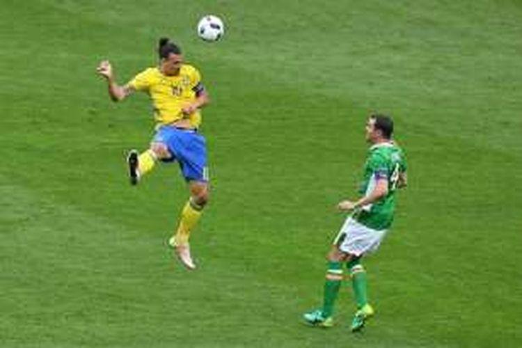 Striker Swedia, Zlatan Ibrahimovic, menyundul bola menjauhi jangkauan bek Irlandia, John O'Shea, saat kedua negara bertemu di Saint-Denis, Senin (13/6/2016).