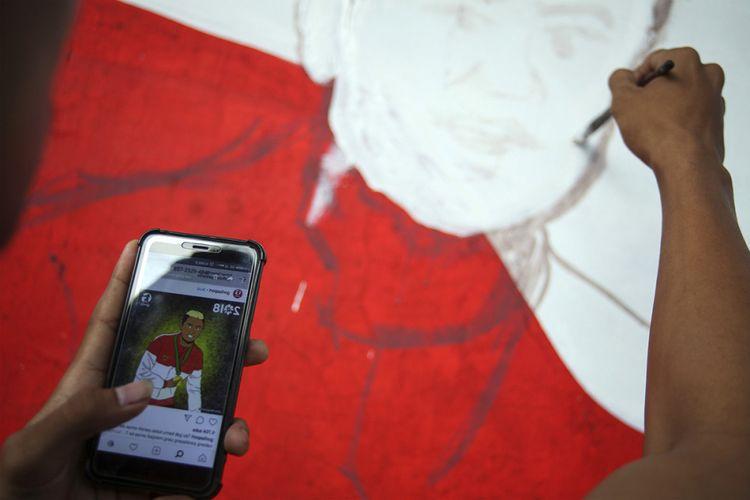 Seniman mural membuat sketsa Atlet paralayang Indonesia Peraih Emas Asian Games 2018 Jafro Megawanto di Kampung Asian Games Pucang Sawit, Solo, Jawa Tengah, Sabtu (25/8/2018). Meskipun tidak bisa mendukung atlet Indonesia secara langsung saat gelaran Asian Games 2018 berlangsung di Jakarta dan Palembang, seniman mural dari Komunitas Mewarnai Indonesia Mural Company di Solo menggambar ekspresi atlet-atlet Indonesia peraih medali emas.
