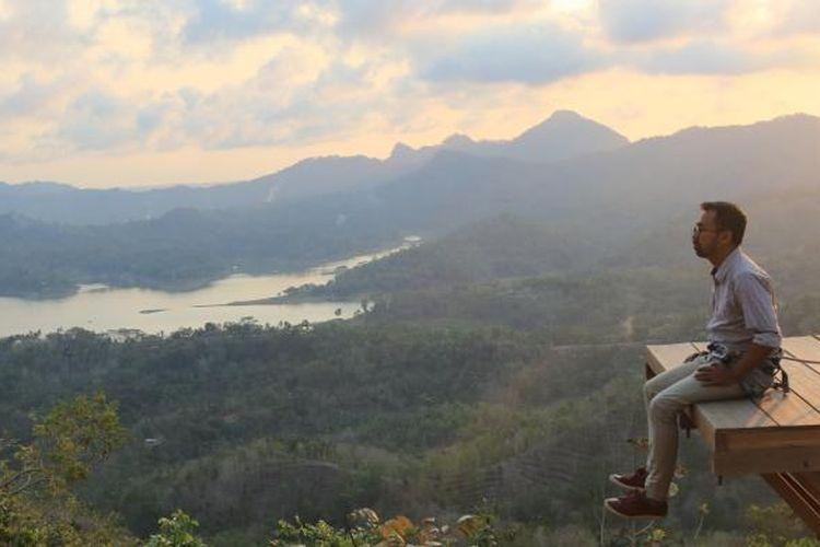 Pengunjung menjajal sensasi berfoto di menara pandang di atas pohon (spot foto), Kamis (8/10/2015). Terlihat dalam latar foto itu Waduk Sermo, perbukitan Menoreh, serta Gunung Susukan dan Gunung Ijo.