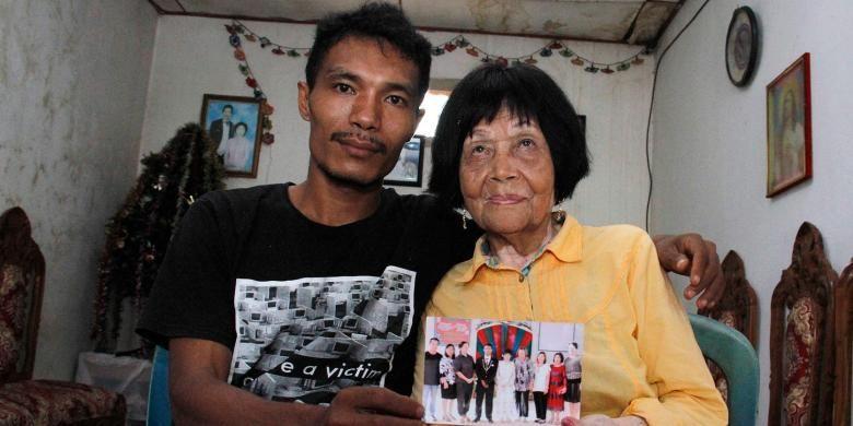 Sofian pemuda berusia 28 tahun memperlihatkan foto pemberkatan nikahnya dengan Martha, nenek yang berusia 82 tahun di Minahasa Selatan, Sulawesi Utara.