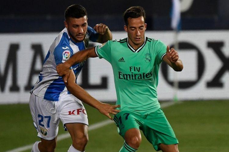 Gelandang Leganes Oscar Rodriguez (kiri) bersaing dengan pemain Real Madrid Lucas Vazquez dalam pertandingan Liga Spanyol Leganes melawan Real Madrid di Estadio Municipal Butarque di Leganes pada 19 Juli 2020.