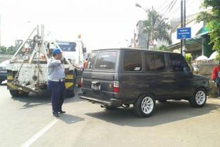 Aparat gabungan dari Dinas Perhubungan, UP Perparkiran, kepolisian dan TNI menertibkan parkir liar di Jalan Matraman Raya, Jakarta Timur, Senin (8/9/2014).
