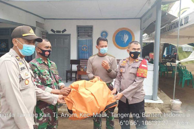 Petugas Polsek Pakuhaji, Kabupaten Tangerang mengevakuasi potongan tubuh yang diduga penumpang pesawat Sriwijaya Air SJ 182 yang ditemukan di sekitar Pantai Kis, Selasa (19/1/2021)