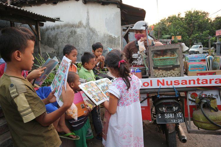 Suasana saat rombong dagang pentol milik Muhammad Lutfan Efendi (29), berhenti di salah satu titik penjualan di Desa Ngudirejo, Kabupaten Jombang, Jawa Timur, Sabtu (27/6/2020). Penjual pentol keliling itu sengaja membawa buku-buku untuk para pelanggannya.