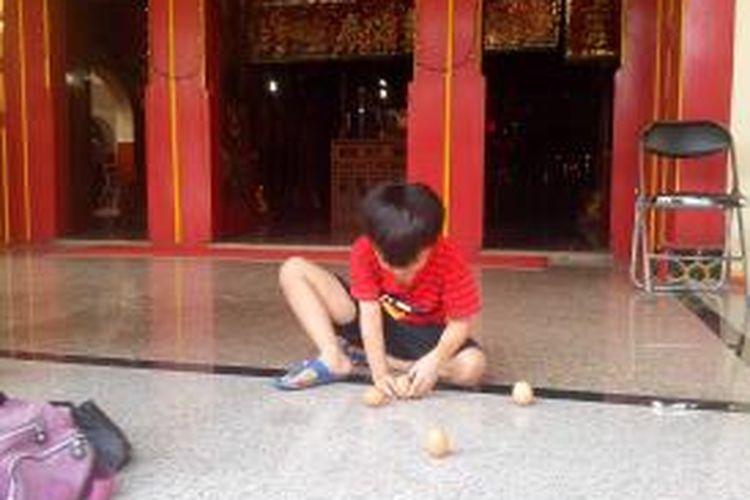 Seorang anak mencoba mendirikan telur dalam perayaan Peng Cun di Klenteng Tjo Hwie Kiong Kota Kediri, Jawa Timur, Senin (2/6/2014).