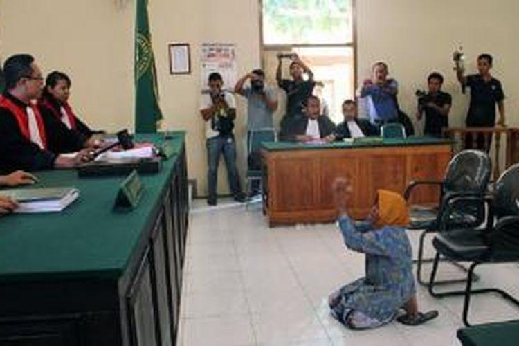 Asyani bersimpuh di depan Majelis Hakim diakhir sidang replik, Kamis (16/4) di Pengadilan Negeri Situbondo. Asyani menangis histeris karena Jaksa menyebutnya mencuri kayu jati. Jaksa penuntut umu menuntutnya hukuman 1 tahun penjara, dengan 18 bulan masa percobaan, dan denda Rp 500 juta subside 1 hari kurungan.