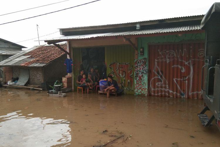 Sejumlah warga tengah duduk di rumah yang terdampak banjir di Dusun Pengasinan Desa Karangligar, Kecamatan Telukjambe Barat, Kabupaten Karawang, Rabu (1/1/2019).