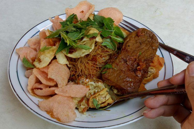 Seporsi Nasi Ulam Misjaya ini menggunakan bubuk kacang, lalu bihun, kerupuk merah, emping, dan daun kemangi. Setelah itu diguyur kuah semur berbumbu sebelum diberi aneka lauk.