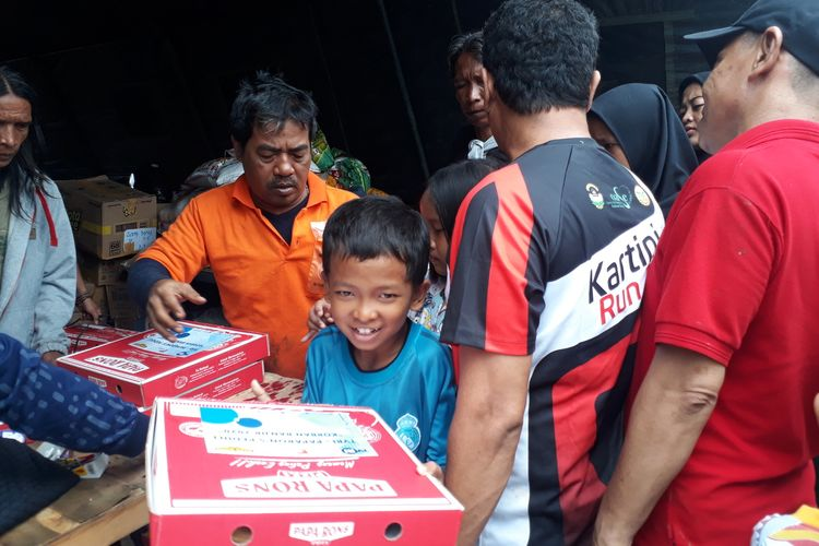 Warga Kampung Pulo, Kelurahan Kampung Melayu, Jatinegara, Jakarta Timur, saat terima bantuan makanan berupa pizza di posko logistik, Jalan Jatinegara Barat, Minggu (5/1/2020).