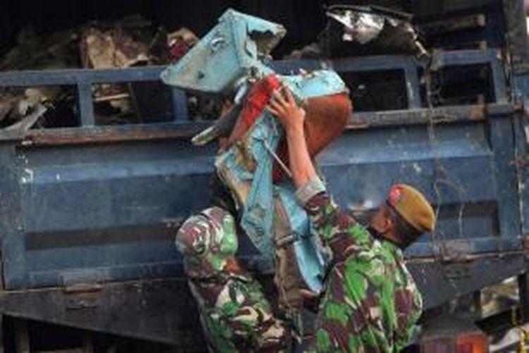 Anggota TNI memasukkan kursi pesawat yang ditemukan di antara puing pesawat Hercules C-130 TNI AU, 1 Juli 2015. Pesawat Jatuh pada Selasa di Jalan Jamin Ginting, Medan, dua menit setelah lepas landas dari Pangkalan Udara Soewondo pukul 12.08.